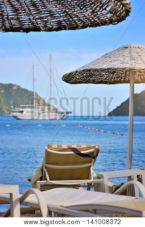 Beach With Umbrella And Sunbeds Against The Backdrop Of The Sea And Boats