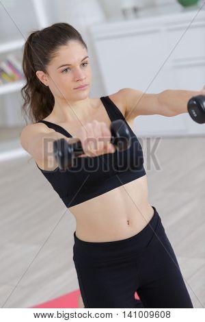 glamorous model holding dumbbell in living room