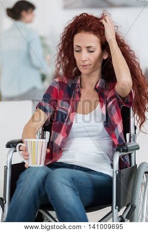 cheerful crippled lady on wheelchair with cup of tea