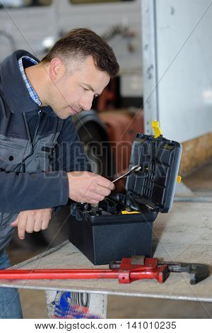 worker picking up a wrench in toolbox