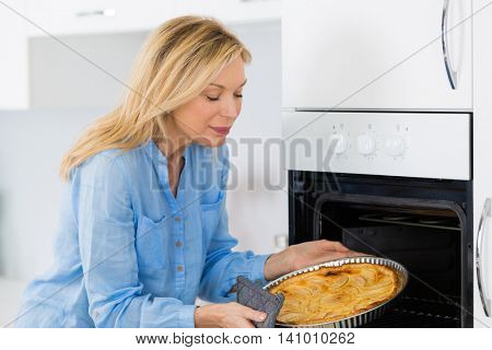 smiling woman cooking apple pie in the oven