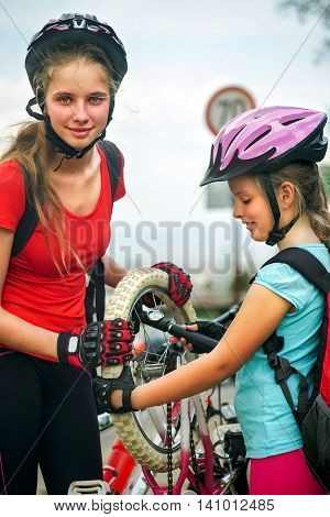 Children girls wearing bicycle helmet with hand pump for bicycle. Girl pump up bicycle tire. Road and traffic sign at background and sky.