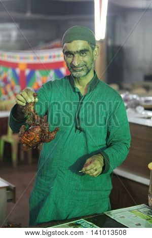 Pune, India - July 11, 2015: A cook holds a delicious tandoori chicken during the ramadan feast in India