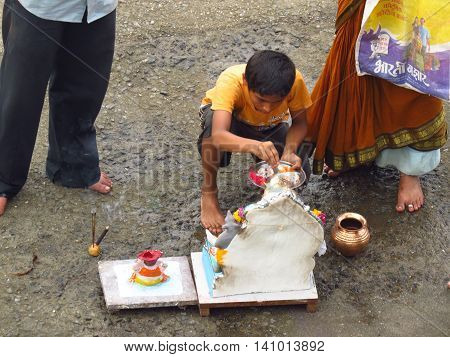Pune, India - September 13, 2013: A young boy performs the traditional ritual of Lord Ganesh during Ganesh festival.
