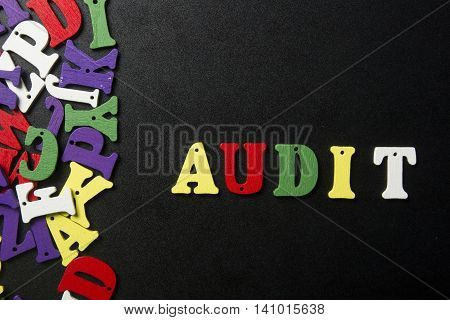 AUDIT word written on colorful wooden abc letter