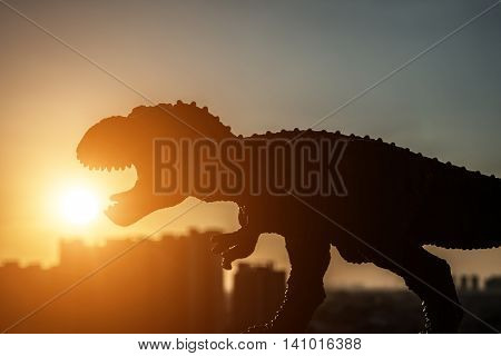 silhouette of tyrannosaurus and buildings in sunset time