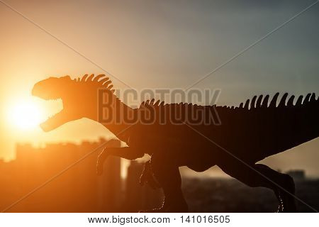 silhouette of allosaurus and buildings in sunset time