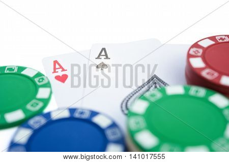 two Ace of pokers beside casino chips on white with clipping path