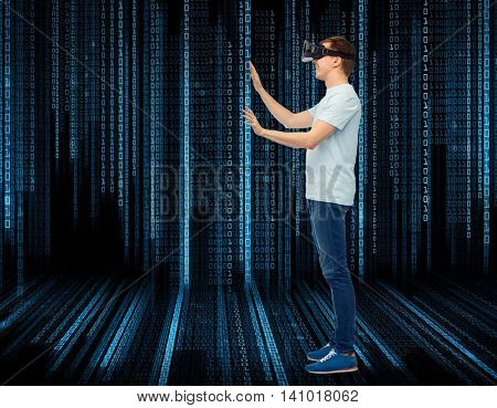 technology, entertainment, cyberspace and people concept - happy young man with virtual reality headset or 3d glasses playing game and touching something over black background with binary code