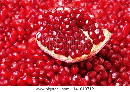 Red fresh piece of pomegranate closeup on a background grains