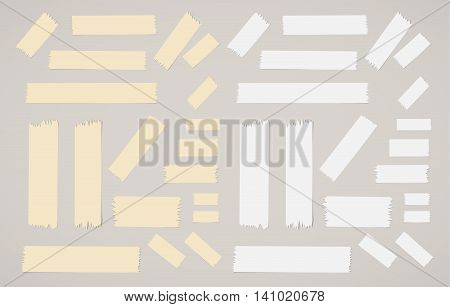 Pieces of different size sticky, adhesive masking tapes are on gray background.