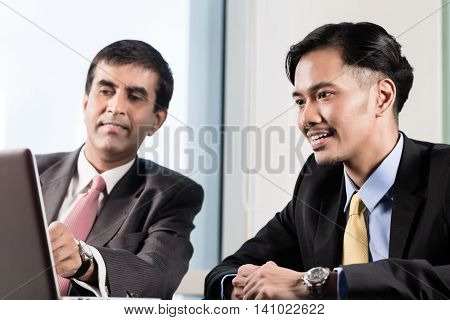 Senior manager and junior professional having business meeting and looking on notebook computer in office