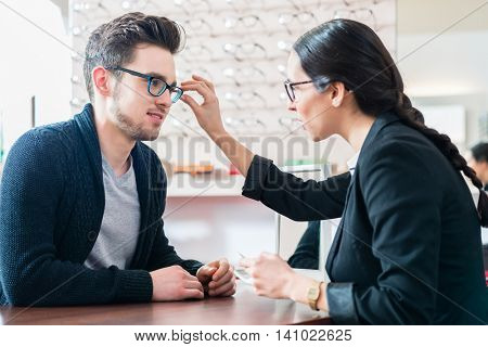 Man in optician shop getting advice from saleswoman buying new glasses