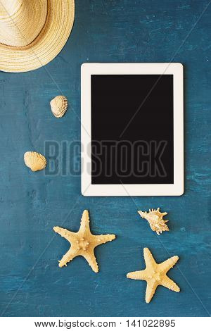 White tablet with blank screen a straw hat shells and starfish on blue surface top view. Summer background