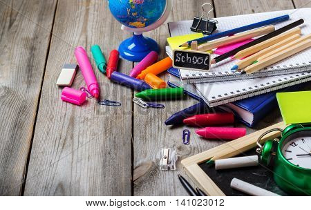 Still life, business, education concept. Office and school supplies, stationery, alarm clock and chalkboard on a rustic wooden table. Selective focus, copy space background