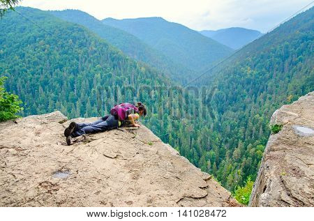 SLOVAK PARADISE, SLOVAKIA - AUGUST 17, 2015: A tourist on the precipice with mountains in the background. Young woman on the precipice in Slovak Paradise National Park.
