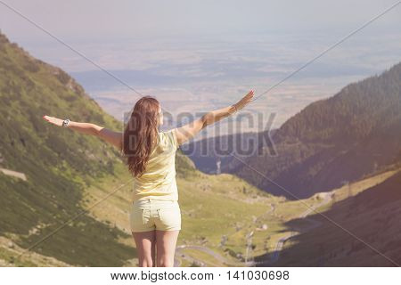 Trekking woman on the peak of Fagaras Mountains, above Transfagarasan highway. Young woman standing on a mountain top with outstretched arms. Vintage look