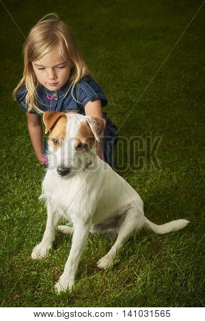 Cute little blond girl playing with her dog Jack Russell Parson Terrier.