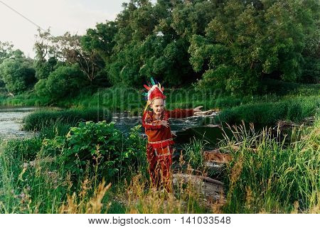 a little boy in a red suit Indian standing by the river with threshold and happily waving his arms