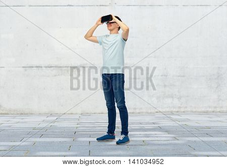 3d technology, virtual reality, entertainment, cyberspace and people concept - happy young man with virtual reality headset or 3d glasses over street background
