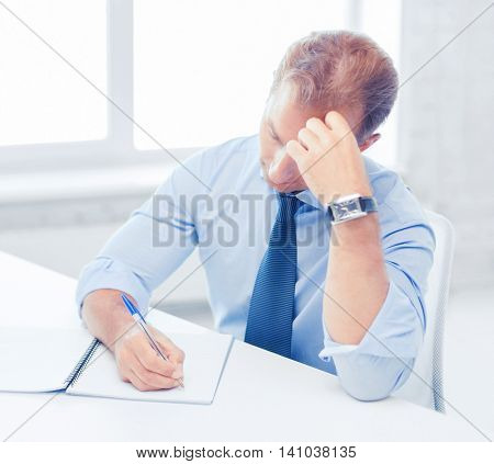 business, office, education and school concept - stressed businessman with notebook and computer