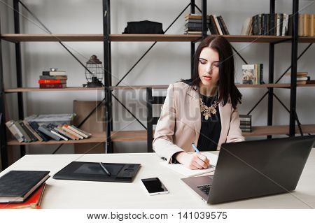 Business woman looking at her phone while working. Receiving message on cellphone, smartphone with blank screen