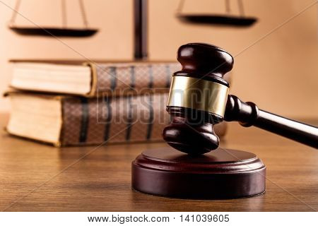 Close-up of wooden gavel with pile of books and golden scales of justice on background