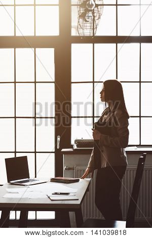 Modern office interior, comfortable workplace. Female manager in big successful company, end of workday, sunset