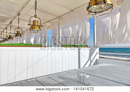 Seaview Restaurant Interior. White Terrace With Wooden Furniture And Lanterns