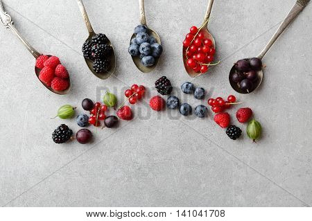 Mixed Berries In Spoons On Slate Background