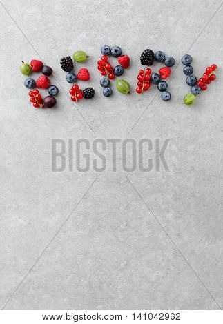 Mixed Berries Shaped As A Letters On Concrete Background