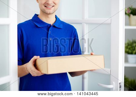 Delivery service worker in uniform delivering parcel