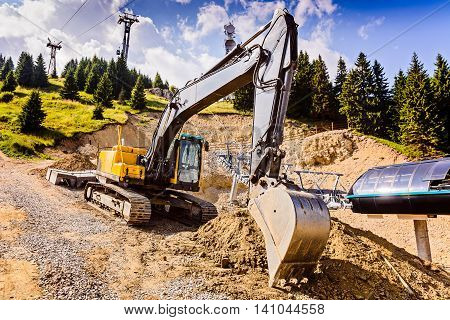 Yellow excavator on tracks while working in the mountains