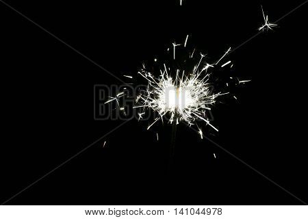 Photograph of the sparkler with bright sparks isolated on a black background