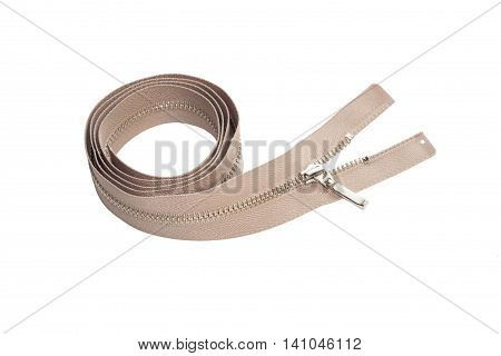 Beige metallic zipper rolled into a hank and isolated on white background.