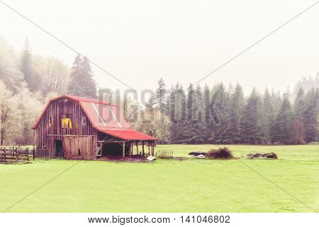 Red barn on a misty and rainy morning in the Pacific Northwest outside Portland