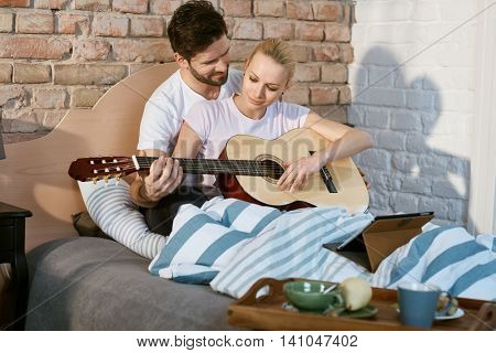 Romantic young couple playing the guitar in bed together.