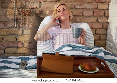 Young woman talking on mobilephone, having breakfast in bed.