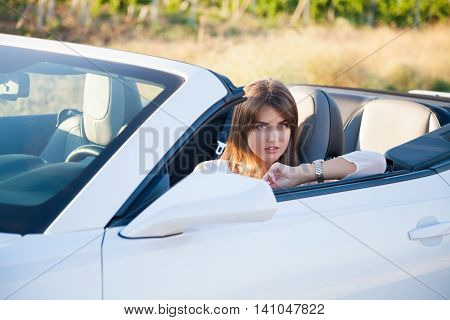 beautiful girl driver sits in white cabriolet