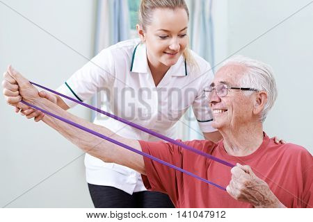 Physiotherapist Helping Senior Male To Use Resistance Band