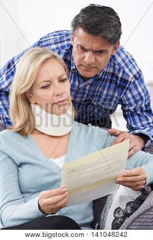 Unhappy Couple Reading Letter About Wife's Injury