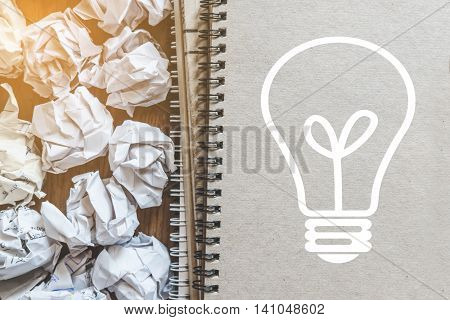 Idea inspiration concepts, crumpled paper balls with light bulb, on binder book
