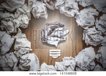 Idea inspiration concepts, crumpled paper balls around light bulb with bright light, on wooden table