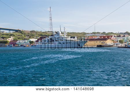Massive luxury yacht docked near bridge on Curacao