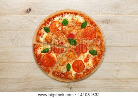 Delicious italian vegetarian pizza Margherita with tomato and cheese, thin pastry crust and one piece cut. Fast food top view at wooden desk on wood table background