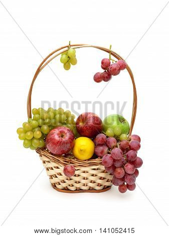 grapes apples and lemon in a wicker basket. white background - horizontal photo.