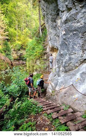 SLOVAK PARADISE SLOVAKIA - AUGUST 17 2015: Tourists on the ladder trail in Slovak Paradise Slovakia.