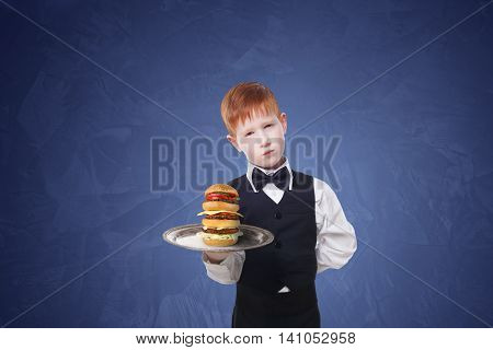 Little sad and tire waiter stands with tray serving big double hamburger. Redhead child boy in suit plays hardworking restaurant servant, gives burger at blue background