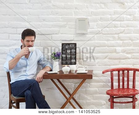 Young man sitting in cafe, drinking coffee.