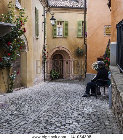 Monforte d'Alba Italy - June 3 2016: Picturesque street in Monforte d'Alba Piedmont Italy with roses colored houses and sittimg woman.
